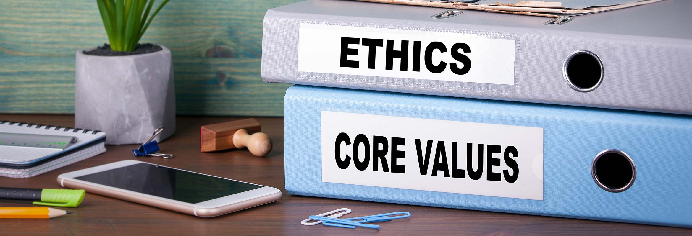 Image of a smartphone and binders with the words ethics and core values.