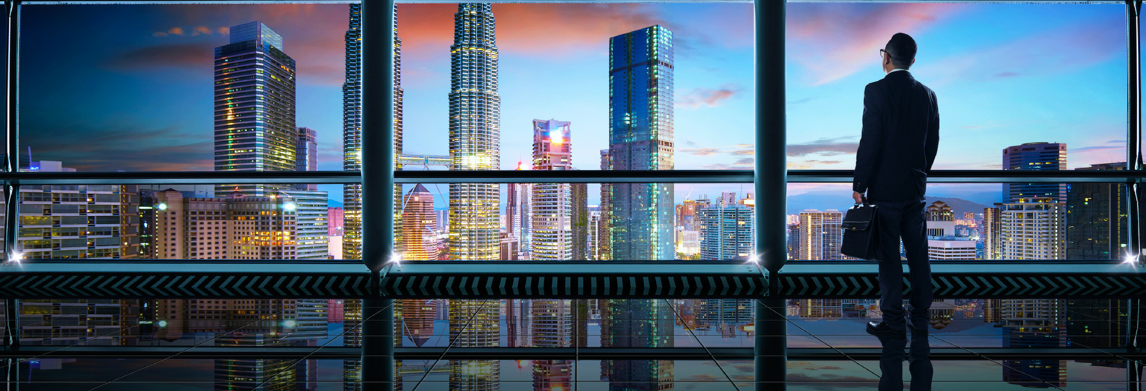 An image of a man in a high rise building look out over the city horizon.