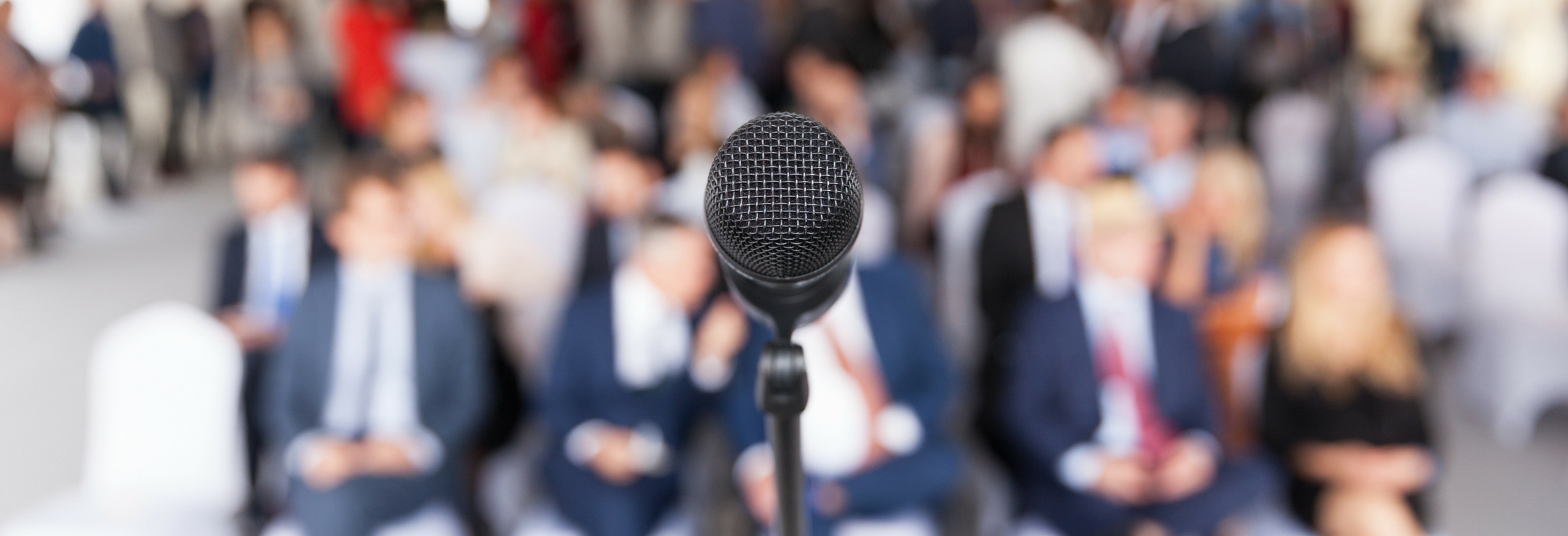 A microphone in a room of executives awaiting a presentation.