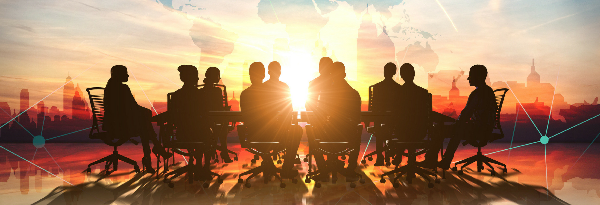 A group of people sitting at a conference table with the sun shining through the window.