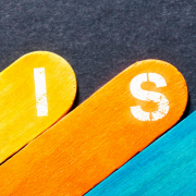 Risk spelled out on individual colored sticks on a black background.