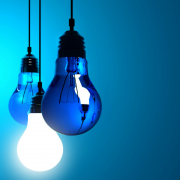 An image of light bulbs hanging on a blue background.